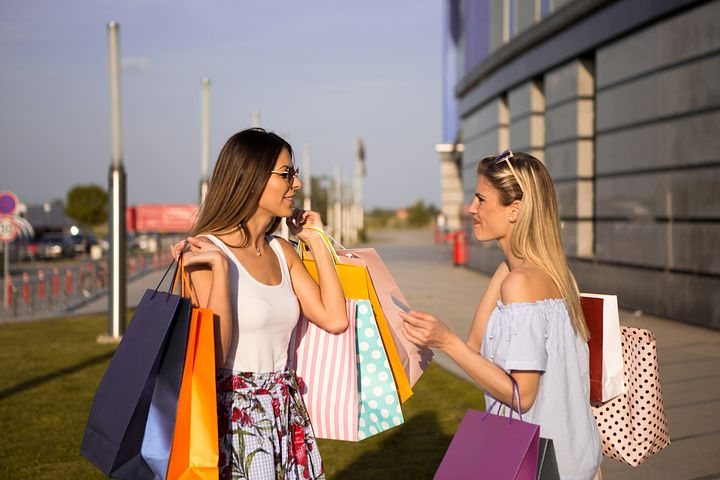two women talking carrying shopping bags