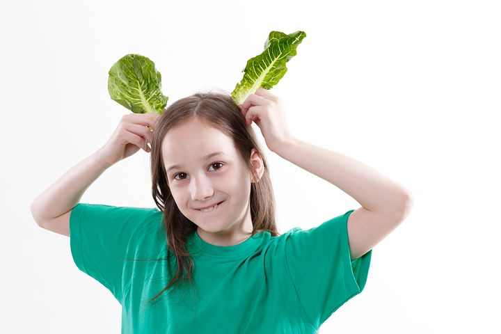 Girl carrying two green leafs on head and posing as Rabbit