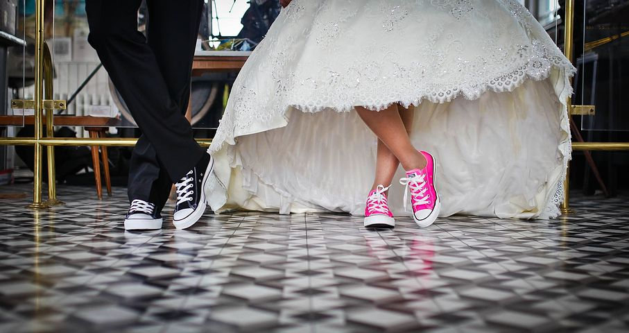 Bride and Groom's formally dressed with Converse shoes half body picture