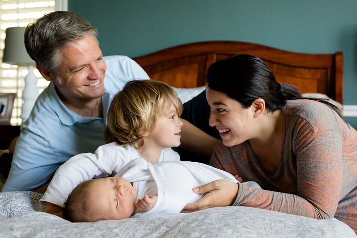 Family picture of mom,dad, toddler and infant smiling