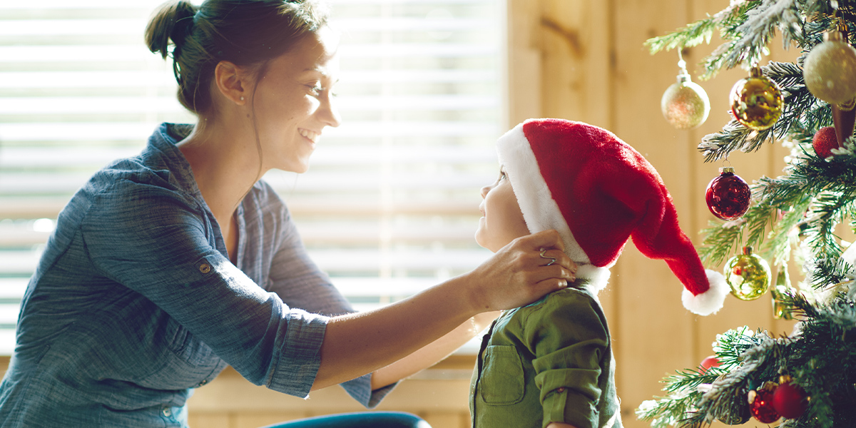 mom putting Christmas Santa hat to baby boy