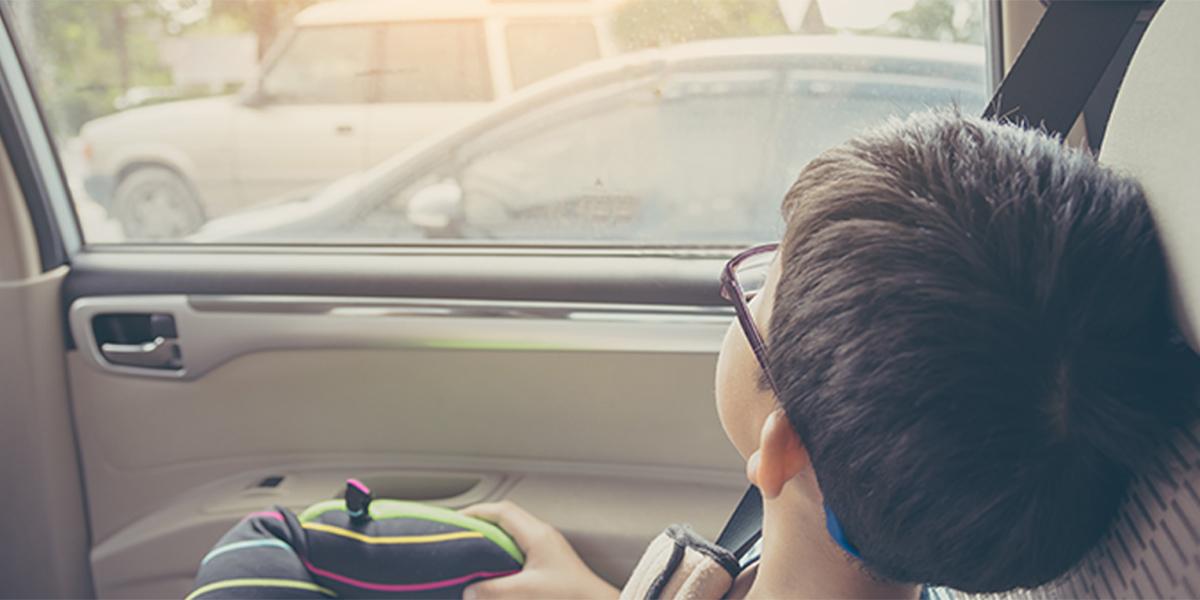 Boy looking outside from car's window