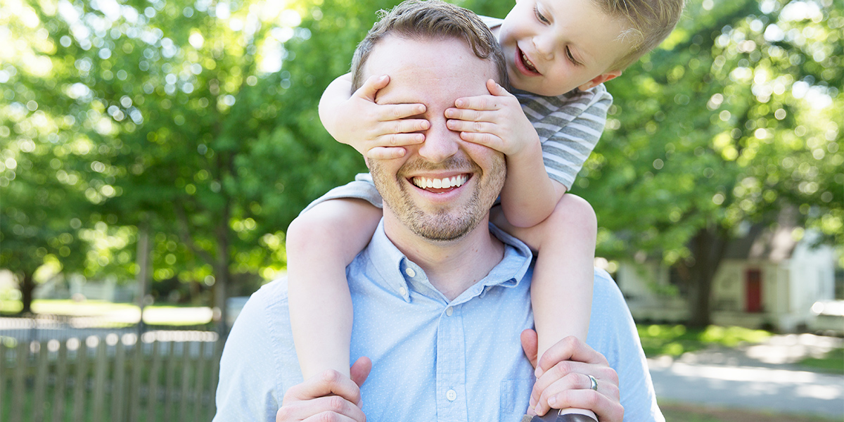 father carrying son in shoulder and son is putting hands in father's eyes