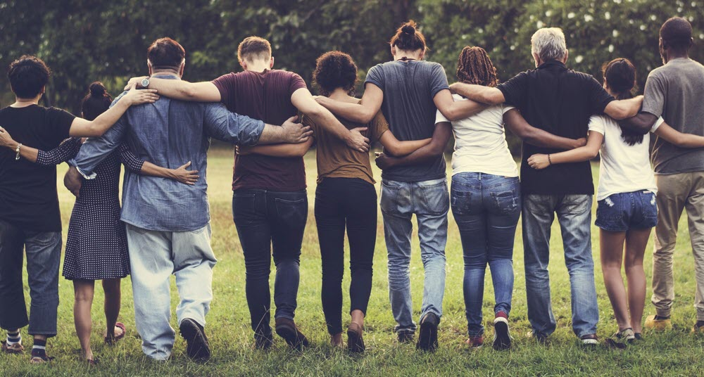 Group of people in a linked in a link with their arms on each other's backs