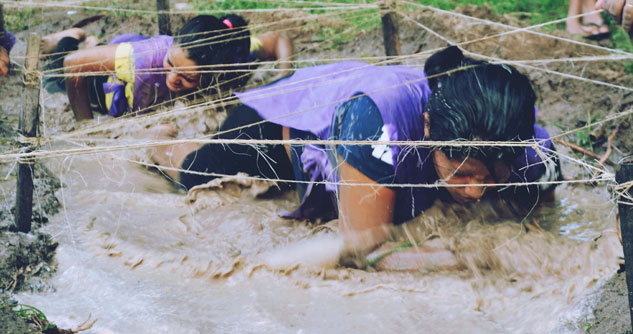 Two women crawling in mud for the Tough Mudder