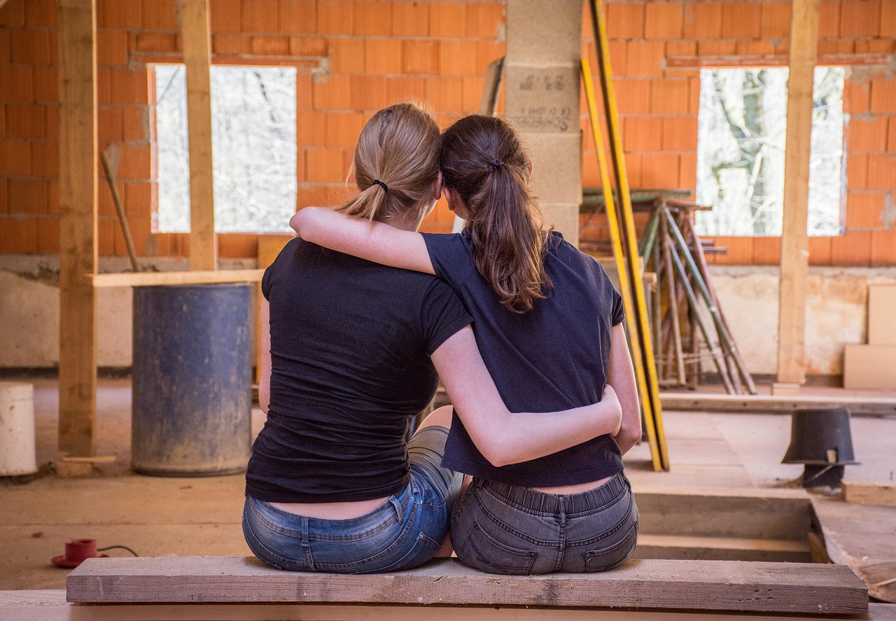 Two women from back picture watching under construction room and hugging