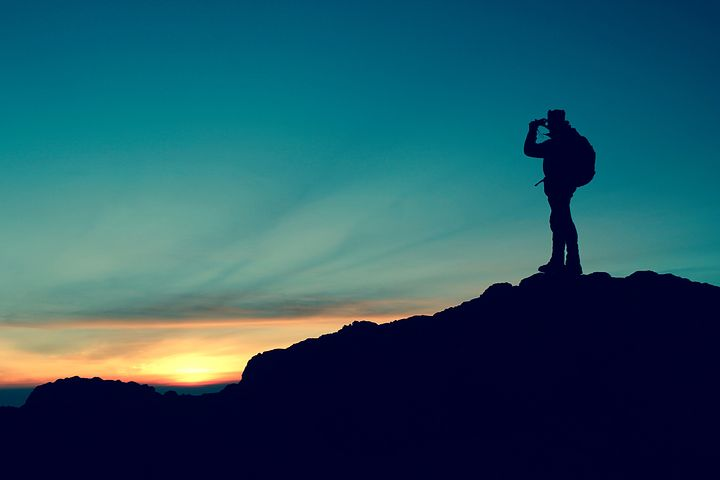 Silhouette sunset image of hiker standing in top of small hill