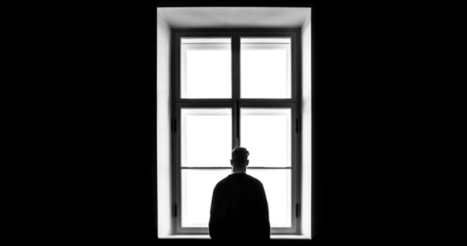 black and white photo of man looking out window