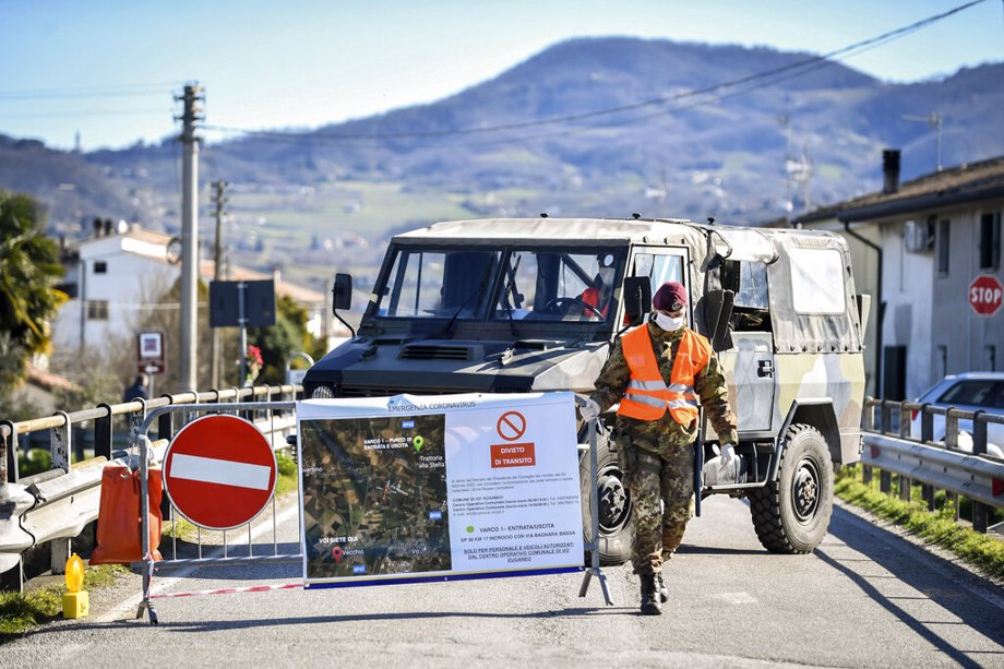 An Italian army soldier blocks off a road leading to the village of Vo'Euganeo, in Italy's northern Veneto region - the epicenter of the Veneto cluster of the new virus