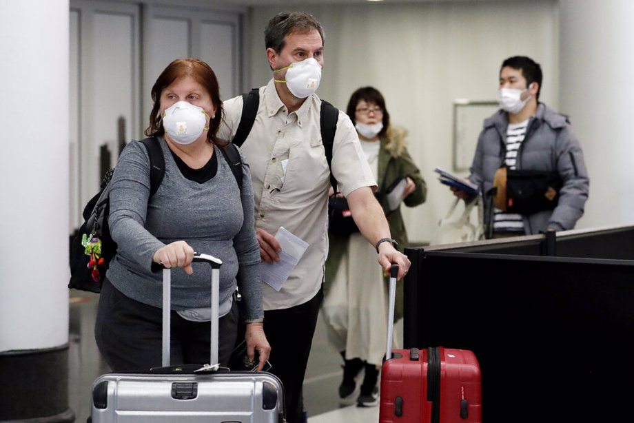 Travelers wear protective mask as they walk through in terminal 5 at O'Hare International Airport in Chicago