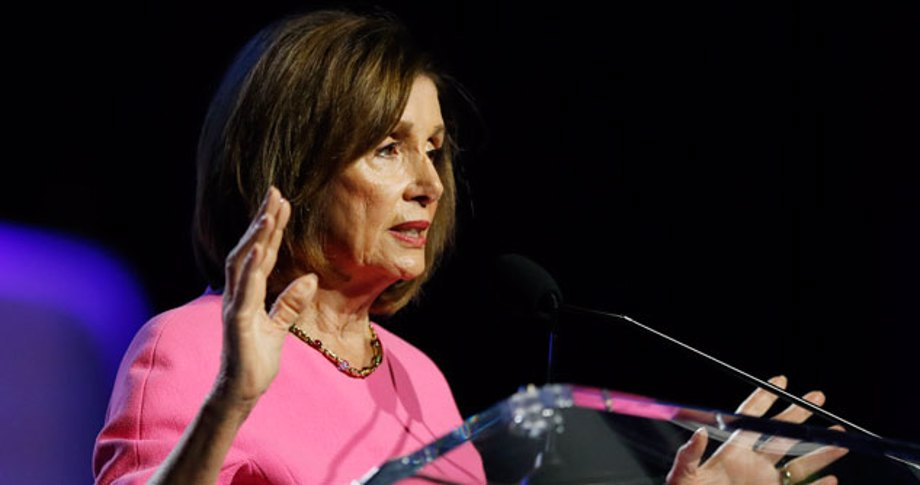 Nancy Pelosi in pink dress with her hands up