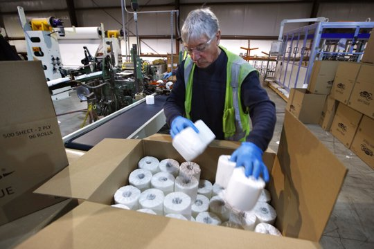 Worker fills box with toilet paper