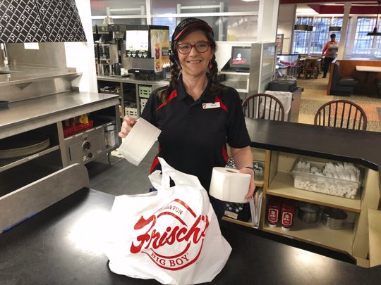 Frisch's Big Boy restaurant employee Nicole Cox bags up an order of toilet paper, among in-demand items including milk and bread the double-decker burger chain is now offering during the coronavirus outbreak in Cincinnati