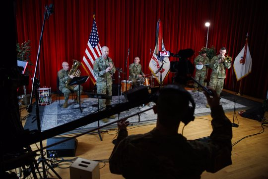 """U.S. Army Field Band members from left, Chief Warrant Officer 2 Kevin Pick, on the tuba, Master Sgt. Bradford Danho, on the clarinet, Staff Sgt. Andrew Emerich, on the drums, Sgt. 1st Class Jonathan Epley, on the banjo and Staff Sgt. Kyle Johnson, on the trombone, are spaced to allow for social distancing as they play during the rehearsal of their daily """"We Stand Ready"""" virtual concert series at Fort George G. Meade in Fort Meade, Md."""