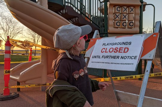child looks at closed playground