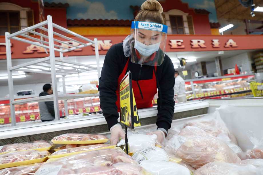 Amid concerns of the spread of COVID-19, a worker stocks poultry at El Rancho grocery store in Dallas, Monday, April 13, 2020.