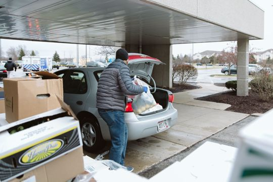 Man loads groceries into car trunk