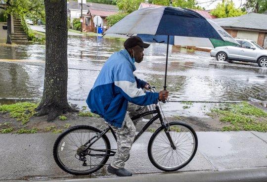 man riding bike with umbrella