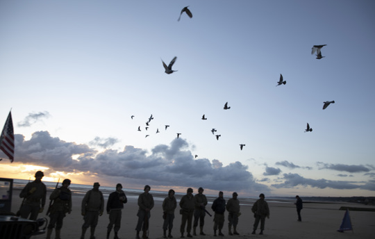 Men in a vintage US WWII uniform watch as pigeons are released during a D-Day 76th anniversary ceremony