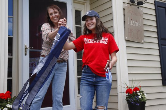 In this June 1, 2020 photo, high school graduate Lizzie Quinlivan and her mom, Julie, hold a Georgetown University windsock at their home in Hingham, Mass. Quinlivan has opted to attend closer-to-home Georgetown instead of colleges on the west coast which were on her original wish-list. As students make college plans for this fall, some U.S. universities are seeing surging interest from in-state students looking to stay closer to home amid the coronavirus pandemic.