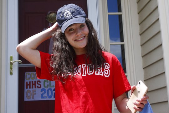 High school graduate Lizzie Quinlivan wears a Georgetown University cap at her home in Hingham, Mass. Quinlivan has opted to attend closer-to-home Georgetown instead of colleges on the west coast which were on her original wish-list.