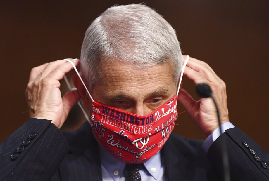 Dr. Anthony Fauci, director of the National Institute for Allergy and Infectious Diseases, lowers his face mask as he prepares to testify before a Senate Health, Education, Labor and Pensions Committee