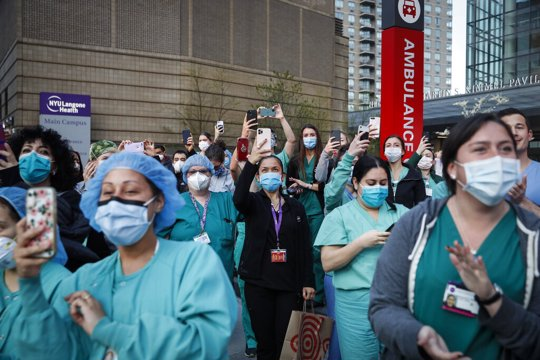 In this April 28, 2020, file photo Medical personnel attend a daily 7 p.m. applause in their honor, during the coronavirus pandemic outside NYU Langone Medical Center in the Manhattan borough of New York. Essential workers are lauded for their service and hailed as everyday heroes. But in most states nurses, first responders and frontline workers who get COVID-19 on the job have no guarantee they'll qualify for workers' comp to cover lost wages and medical care.