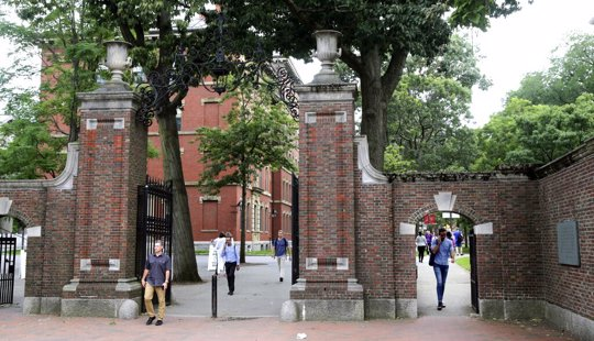 In this Aug. 13, 2019, file photo, pedestrians walk through the gates of Harvard Yard at Harvard University in Cambridge, Mass. Harvard and the Massachusetts Institute of Technology filed a federal lawsuit Wednesday, July 8, 2020, challenging the Trump administration's decision to bar international students from staying in the U.S. if they take classes entirely online this fall. Some institutions, including Harvard, have announced that all instruction will be offered remotely in the fall during the ongoing coronavirus pandemic.