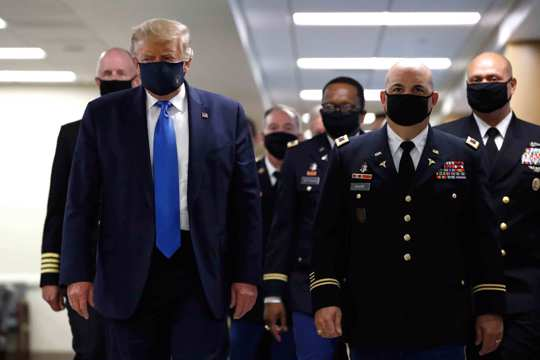 President Donald Trump wears a face mask as he walks down a hallway during a visit to Walter Reed National Military Medical Center in Bethesda, Md.