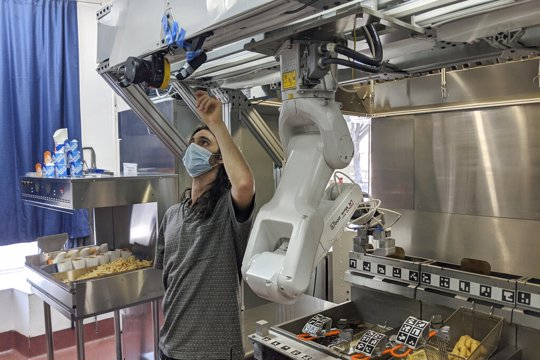 Technician makes an adjustment to a robot at Miso Robotics' White Castle test kitchen in Pasadena, Calif.