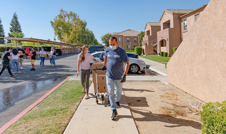 People walking down sidewalk delivering cart of goods