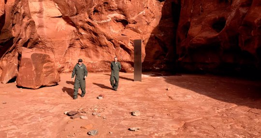 Utah state workers walk near a metal monolith