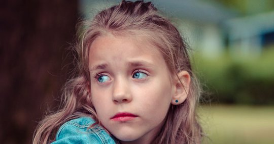 Young girl about 8 years old looks very sad.