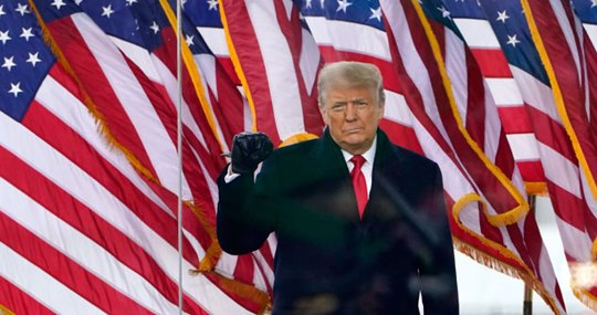 Trump behind a plexiglass and American flags behind him