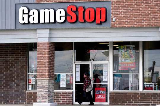 A woman wears a face mask as she walks past a GameStop store in Des Plaines, Ill., Thursday, Oct. 15, 2020.