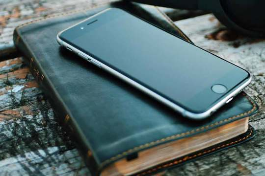 Bible with a smartphone lying on it