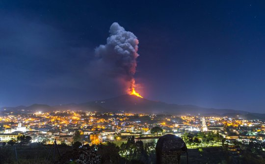 Flames and smoke billowing from a crater, as seen from the southern side of the Mt Etna volcano, tower over the city of Pedara, Sicily