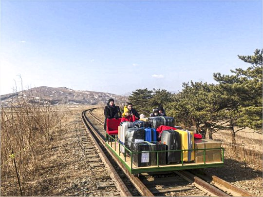 Group of Russian diplomats push hand-pushed rail trolley with their children and suitcases to the border with Russia