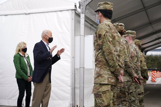 President Joe Biden and first lady Jill Biden meet with troops at a FEMA COVID-19 mass vaccination site at NRG Stadium in Houston