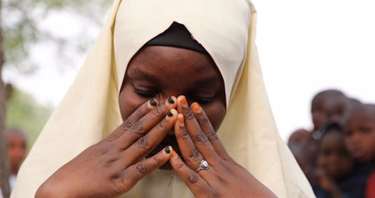 Nigerian schoolgirl with head covering, praying