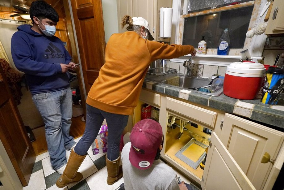 Roberto Valerio Jr., left, and his cousin Hector Valerio, right, look on as homeowner Nora Espinoza test for water coming out of the faucet