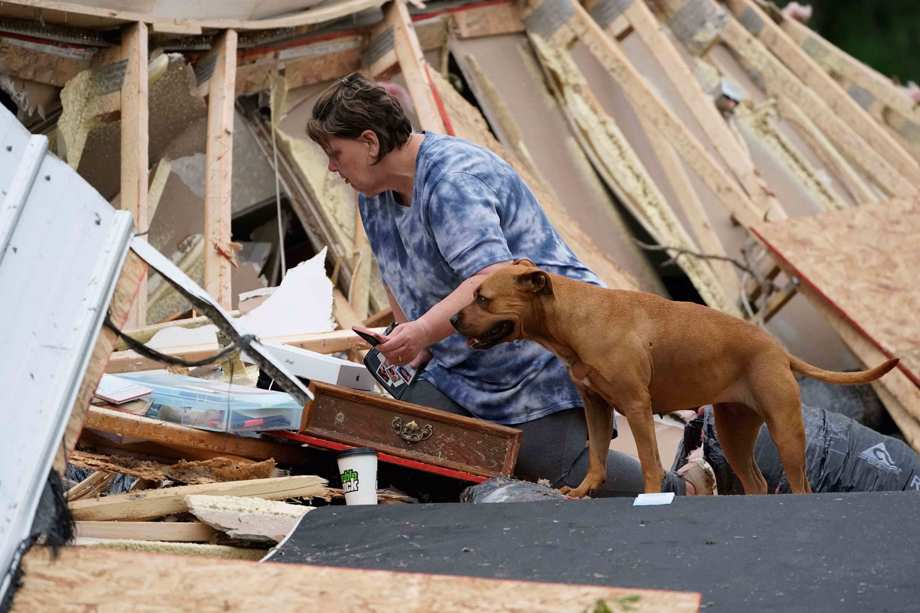 Vickie Savell looks through her belongings amid the remains of her new mobile home early Monday, May 3, 2021, in Yazoo County, Miss.