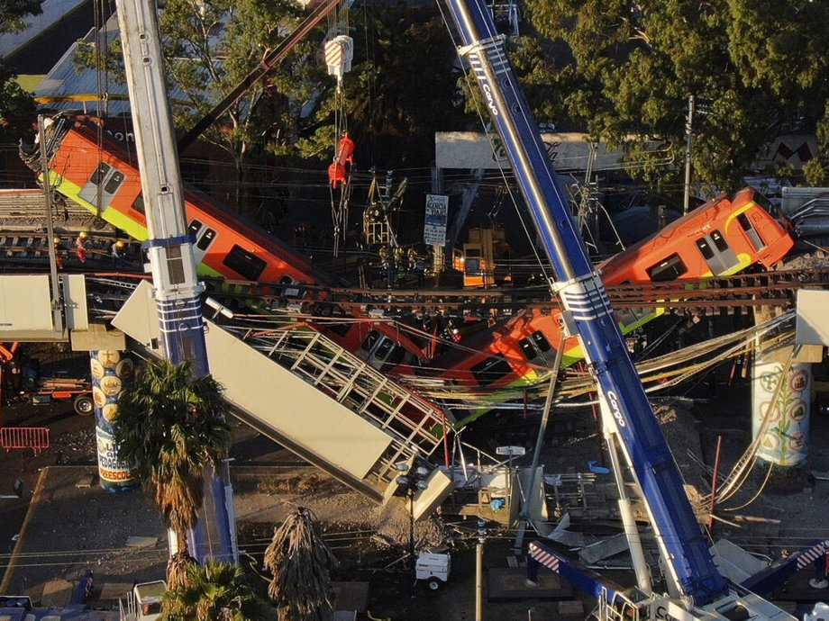 An aerial view of subway cars dangle at an angle from a collapsed elevated section of the metro, in Mexico City