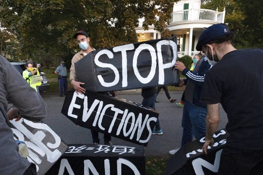 In this Oct. 14, 2020, file photo, housing activists erect a sign in front of Massachusetts Gov. Charlie Baker's house in Swampscott, Mass. A federal judge has ruled, Wednesday, May 5, 2021, that the Centers for Disease Control exceeded its authority when it imposed a federal eviction moratorium to provide protection for renters out of concern that having families lose their homes and move into shelters or share crowded conditions with relatives or friends during the pandemic would further spread the highly contagious virus.