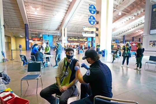 Austin Kennedy, left, a Seattle Sounders season ticket holder, gets the Johnson & Johnson COVID-19 vaccine at a clinic in a concourse at Lumen Field prior to an MLS soccer match between the Sounders and the Los Angeles Galaxy.
