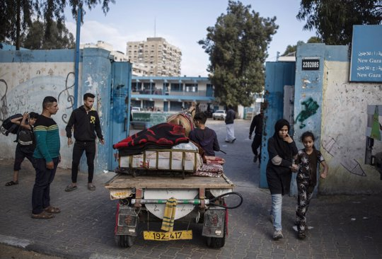 Palestinians flee their homes to a U.N. school after overnight Israeli heavy missile strikes on their neighborhoods in the outskirts of Gaza City