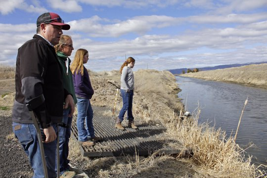 armer Ben DuVal, his wife, Erika, and their daughters, Hannah, 12, in purple, and Helena, 10, in gray, stand near a canal for collecting run-off water near their property in Tulelake, Calif.