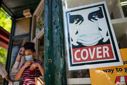 A customer exits a corner market while wearing a protective mask in the retail shopping district of the SoHo neighborhood of the Manhattan borough of New York, Friday, May 14, 2021.