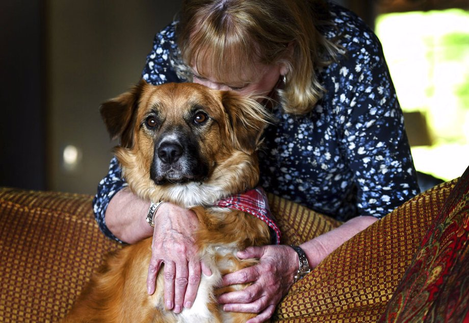Linda Oswald hugs 2-year-old dog Tilly at their home in Hayden, Idaho