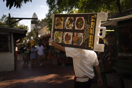 Restaurant worker Abraham Ordaz, 38, carries a menu stand along Olvera Street in Los Angeles, Tuesday, June 8, 2021. Olvera Street has long been a thriving tourist destination and a symbol of the state's early ties to Mexico. The location of where settlers established a farming community in 1781 as El Pueblo de Los Angeles, its historic buildings were restored and rebuilt as a traditional Mexican marketplace in 1930s. As Latinos in California have experienced disproportionately worse outcomes from COVID-19, so too has Olvera Street.